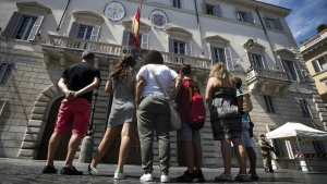People stand beneath the Spanish Embassy to the Holy See where a Spanish flag flies at half-mast as a tribute to the victims of a deadly van attack in Barcelona, in Rome's Piazza di Spagna square, on Aug.18, 2017. (Angelo Carconi / ANSA via AP)
