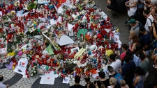 People gather at a memorial tribute of flowers, messages and candles to the victims on Barcelona's historic Las Ramblas promenade on the Joan Miro mosaic, embedded in the pavement where the van stopped after killing at least 13 people in Barcelona , Spain, Friday, Aug. 18, 2017. (AP / Manu Fernandez)