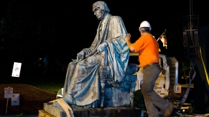 Workers sits the monument dedicated to U.S. Supreme Court Chief Justice Roger Brooke Taney on a flatbed truck after it was removed from outside the Maryland State House, in Annapolis, Md., early Friday, Aug. 18, 2017. (AP / Jose Luis Magana)