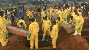 Volunteers handle a coffin during a mass funeral for victims of heavy flooding and mudslides in Regent at a cemetery in Freetown, Sierra Leone, Thursday, Aug. 17, 2017. (AP / Manika Kamara)