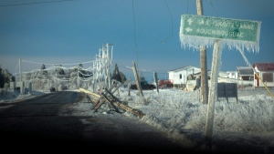 Downed power poles and an ice covered sign are shown in Escuminac, N.B., on Friday, Jan. 27, 2017. (Diane Doiron / THE CANADIAN PRESS)