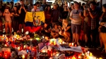 People gather at a memorial tribute of flowers, messages and candles to the victims on Barcelona's historic Las Ramblas promenade on the Joan Miro mosaic, embedded in the pavement where the van stopped after killing at least 13 people in Barcelona , Spain, Friday, Aug. 18, 2017. Spanish police on Friday shot and killed five people carrying bomb belts who were connected to the Barcelona van attack as the manhunt intensified for the perpetrators of Europe's latest rampage claimed by the Islamic State group. (AP Photo/Manu Fernandez)