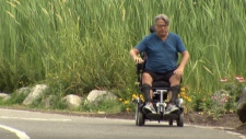 Richard Kipping demonstrates how his wheelchair shakes after it was damaged. (CTV)
