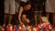 A woman lights up a candle in a memorial tribute to the victims of the terrorist attack on the historic street of Las Ramblas one day after the terrorist attack, in Barcelona, Spain, Friday Aug. 18, 2017. Police on Friday shot and killed five people carrying bomb belts who were connected to the Barcelona van attack, as the manhunt intensified for the perpetrators of Europe's latest rampage claimed by the Islamic State group. (AP Photo/Santi Palacios)