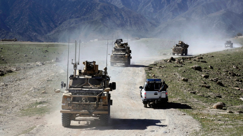 FILE - In this Saturday, April 17, 2017 file photo, U.S. forces and Afghan commando patrol Pandola village near the site of a U.S. bombing in the Achin district of Jalalabad, east of Kabul, Afghanistan. (AP Photo/Rahmat Gul, file)