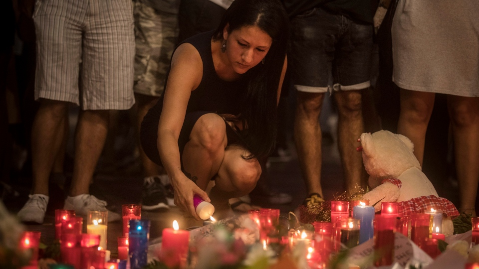 A woman lights up a candle in a memorial tribute to the victims of the terrorist attack on the historic street of Las Ramblas one day after the terrorist attack, in Barcelona, Spain, Friday Aug. 18, 2017. (AP Photo/Santi Palacios)