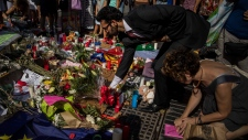 A man leaves flowers in a memorial tribute to the victims of the terrorist attack on the historic street of Las Ramblas, in Barcelona, Spain, Friday Aug. 18, 2017. Police on Friday shot and killed five people carrying bomb belts who were connected to the Barcelona van attack, as the manhunt intensified for the perpetrators of Europe's latest rampage claimed by the Islamic State group. (AP Photo/Santi Palacios)