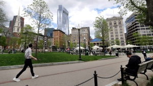 n this May 3, 2017 photo, people sit and walk in the Boston Common, a park surrounded by buildings in downtown Boston. (AP Photo/Elise Amendola)