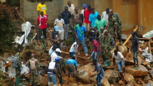 FILE- In this Tuesday, Aug.15, 2017 file photo, volunteers search for bodies from the scene of heavy flooding and mudslides in Regent, just outside of Sierra Leone's capital Freetown. (AP Photo/ Manika Kamara, File)