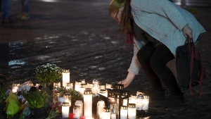 A woman places a memorial candle at the Market Square for the victims of Friday's stabbings in Turku, Finland, on Friday evening, Aug. 18, 2017. Several people were stabbed on the Market Square on Friday. (Vesa Moilanen/Lehtikuva via AP)