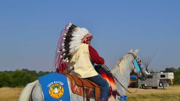 In this Friday, Aug. 18, 2017, photo, a boy wearing a traditional headdress rides through the Crow Fair grounds in Crow Agency, Mont. (Mary Hudetz/AP Photo)