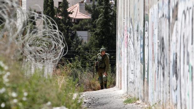 An Israeli soldier is seen near the separation barrier in Bethlehem PSE Friday, July 28, 2017. (Nasser Shiyoukhi/AP Photo)