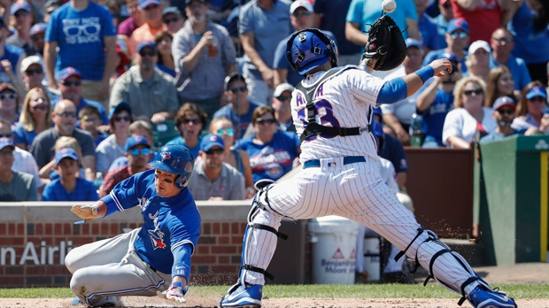 Toronto Blue Jays' Darwin Barney, left, scores as Chicago Cubs' Alex Avila, right, waits for the ball during the fourth inning of a baseball game, Saturday, Aug. 19, 2017, in Chicago. (AP Photo/Kamil Krzaczynski)