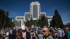 Police officers walk through the crowd as thousands of people gather outside Vancouver City Hall as alt-right protesters and anti-racism protesters take part in opposing rallies in Vancouver, B.C., on Saturday August 19, 2017. (THE CANADIAN PRESS / Darryl Dyck)