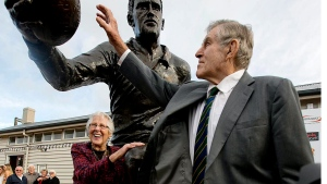 Former All Black Sir Colin Meads reaches up to touch the statue of himself with his wife Verna at the unveiling in Te Kuiti, New Zealand, Monday, June 19, 2017. (Alan Gibson / New Zealand Herald via AP)