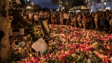 People gather at a memorial tribute of flowers, messages and candles to the victims on Barcelona's historic Las Ramblas, two days after the vehicle attacks, in Barcelona, Spain, Friday Aug. 18, 2017. Authorities in Spain and France pressed the search Saturday for the supposed ringleader of an Islamic extremist cell that carried out vehicle attacks in Barcelona and a seaside resort, as the investigation focused on links among the Moroccan members and the house where they plotted the carnage.(AP Photo/Santi Palacios)