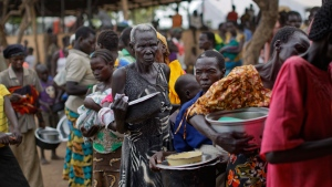 FILE - In this Tuesday, June 6, 2017 file photo, South Sudanese refugees queue to receive a lunch of maize mash and beans, at the Imvepi reception centre, where newly arrived refugees are processed before being allocated plots of land in nearby Bidi Bidi refugee settlement, in northern Uganda. The number of South Sudanese refugees sheltering in Uganda has reached 1 million, the United Nations said Thursday, Aug. 17, 2017, a grim milestone in what has become the world's fastest-growing refugee crisis. (AP Photo/Ben Curtis, File)