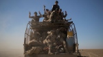 FILE - In this Nov. 20, 2016 file photo, Popular Mobilization Units fighters ride on the back of a truck on their way to fight against Islamic State militants in the airport of Tal Afar, west of Mosul, Iraq. (AP Photo/Felipe Dana, File)