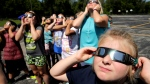 In this photo taken Friday, Aug. 18, 2017, fourth graders at Clardy Elementary School in Kansas City, Mo. practice the proper use of their eclipse glasses in anticipation of Monday's solar eclipse. Schools around the country preparing for the solar eclipse are reacting in a variety ways, with some using the event for a full day of science lessons and others closing to avoid the crush of crowds expected in their towns. (AP Photo/Charlie Riedel)