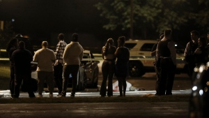 In this Sunday, Aug. 20, 2017, photo, a group of people and police officers stand near the body of a man fatally shot in the parking lot of an event center in Chicago. (John J. Kim/Chicago Tribune via AP)