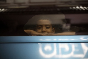 A boy looks out the window of a private bus used by Mexican authorities to transport a large group of Central American migrants to a migrant detention facility in Veracruz, Mexico, late Saturday, Aug. 19, 2017.  (AP Photo/Felix Marquez)