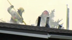 Firefighters on the roof of a home in the 1700 block of 24 Ave. N.W. during Sunday morning's response