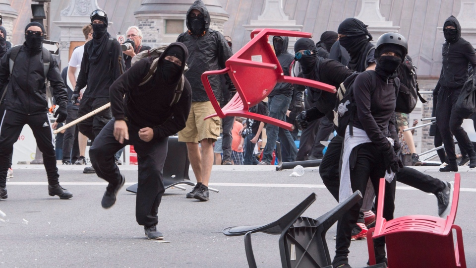 A Black Bloc protester throws a chair during an anti-racism demonstration, in Quebec City on Sunday, August 20, 2017. (THE CANADIAN PRESS/Jacques Boissinot)