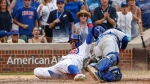 Chicago Cubs' Javier Baez, left, scores as Toronto Blue Jays' Raffy Lopez, right, applies a late tag during the 10th inning of a baseball game, , in Chicago, on Sunday, Aug. 20, 2017. (AP Photo/Kamil Krzaczynski)