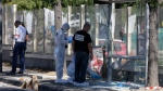 Police officers inspect a bus stop in La Valentine district after a van rammed into two bus stops in the French port city of Marseille, southern France, Monday Aug.21, 2017. (AP Photo/Claude Paris)