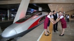 In this June 26, 2017 file photo, railway workers pose for photos with the Fuxing, China's latest high speed train capable of reaching 400 km/h during its maiden service from Beijing. (Chinatopix Via AP, File)