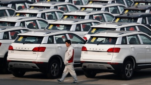 In this Feb. 19, 2017, file photo, a worker walks past Haval SUV models parked outside the Great Wall Motors assembly plant in Baoding in north China's Hebei province. (Andy Wong/AP)