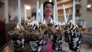 Tour guide Julie R. carries servings of soft serve ice cream to customers during a gourmet ice cream food tour in Vancouver, B.C., on Thursday August 17, 2017. (THE CANADIAN PRESS/Darryl Dyck)