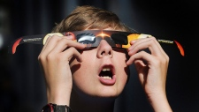 In this Wednesday, Aug. 16, 2017 photo, Colton Hammer tries out his new eclipse glasses he just bought from the Clark Planetarium in Salt Lake City in preparation for the Aug. 21 eclipse. (Scott G Winterton/The Deseret News via AP)