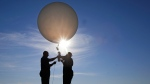 Mike Newchurch, left, professor of atmospheric chemistry at the University of Alabama in Huntsville, and graduate student Paula Tucker prepare a weather balloon before releasing it to perform research during the solar eclipse Monday, Aug. 21, 2017, on the Orchard Dale historical farm near Hopkinsville, Ky. The location, which is in the path of totality, is also at the point of greatest intensity. (AP Photo / Mark Humphrey)