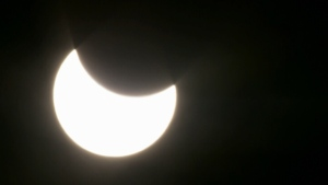 A view as the moon begins to cover the sun during a total solar eclipse.