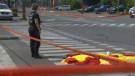 A police officer stands beside the body of a pedestrian who was killed when a truck driver went through a green light without realizing a woman was still walking across the street (Aug. 21, 2017)