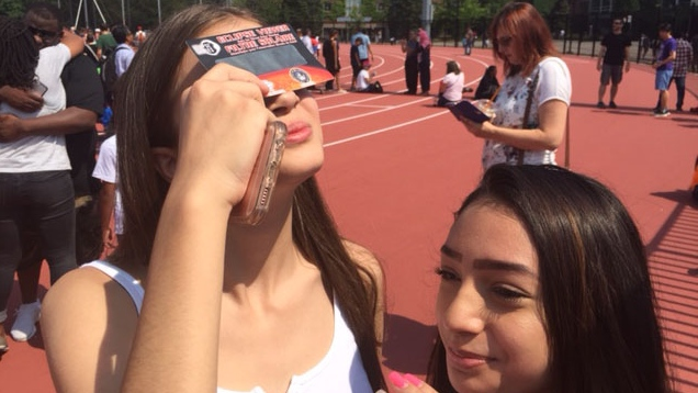 Young women view the partial solar eclipse at York University in Toronto, on Monday, Aug. 21, 2017. (John Musselman / CTV Toronto)