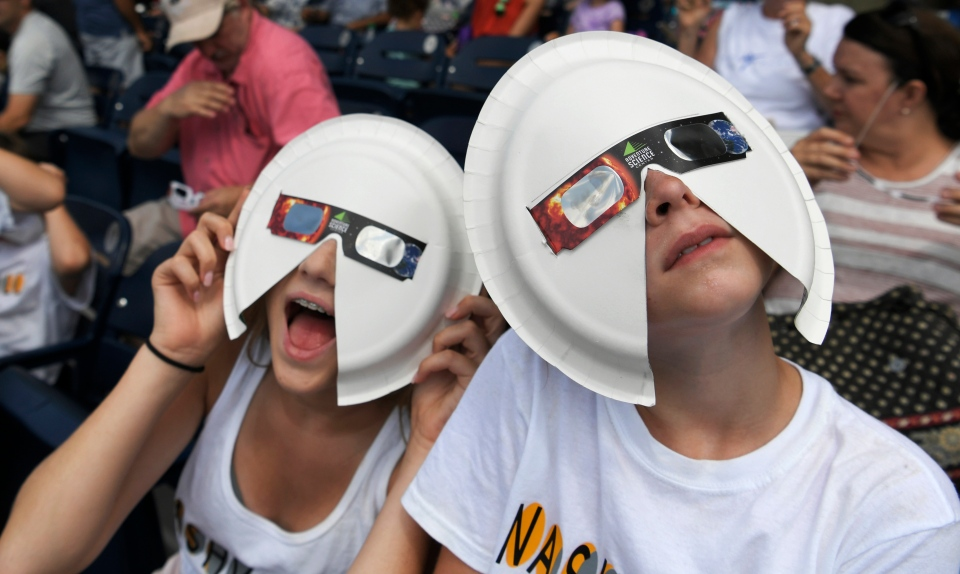 Annie Gray Penuel and Lauren Peck, both of Dallas, wear their makeshift eclipse glasses at Nashville's eclipse viewing party ahead of the solar eclipse at First Tennessee Park on Monday, Aug. 21, 2017, in Nashville, Tenn. (Shelley Mays / The Tennessean via AP)