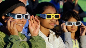 Schweta Kulkarni, from left, Rhea Kulkarni and Saanvi Kulkarni, from Seattle, try out their eclipse glasses on the sun at a gathering of eclipse viewers in Salem, Ore., early Monday, Aug. 21, 2017. (AP Photo/Don Ryan)