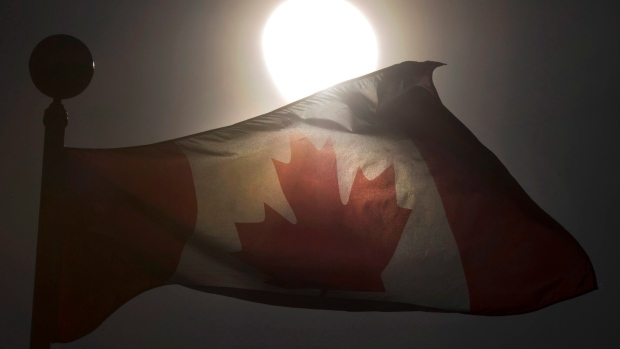 A Canadian flag flutters in Toronto in front of a partial solar eclipse on Monday August 21, 2017. (The Canadian Press/Frank Gunn)