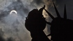 A partial solar eclipse appears over the Statue of Liberty on Liberty Island in New York, Monday, Aug. 21, 2017. (AP Photo / Seth Wenig)