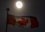 A Canadian flag flutters in Toronto in front of a partial solar eclipse on Monday August 21, 2017. THE CANADIAN PRESS/Frank Gunn