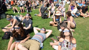 Observers watch the solar eclipse at the Canadian National Exhibition in Toronto. (THE CANADIAN PRESS / Jon Blacker)