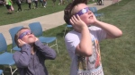 A couple of youngsters try out their solar glasses while waiting to take in the eclipse on Monday, August 21, 2017. (Marek Sutherland / CTV London)