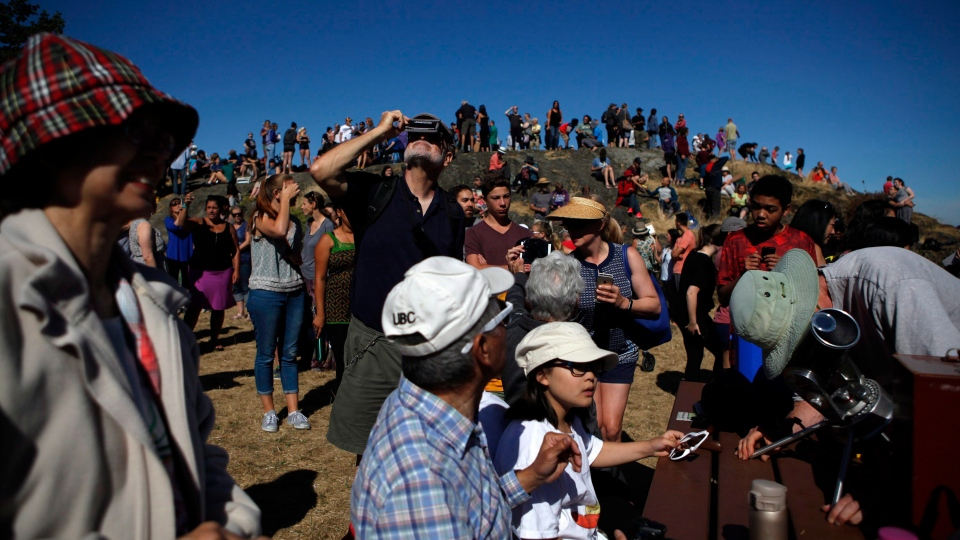 Hundreds of people gathered at Mount Tolmie to take in the partial solar eclipse in Victoria, B.C., on Monday, August 21, 2017. (THE CANADIAN PRESS/Chad Hipolito)