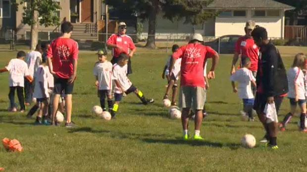 Coaches and kids run drills at camp