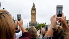 People record the last bell bong at Elizabeth Tower in London, Monday, Aug. 21, 2017. At noon, Big Ben's famous bongs sounded for the last time before major conservation works are carried out. The Elizabeth Tower, home to the Great Clock and Big Ben, is currently undergoing a complex programme of renovation work that will safeguard it for future generations. While this vital work takes place, the Great Bell's world famous striking will be paused until 2021 to ensure the safety of those working in the Tower.(AP Photo/Frank Augstein)