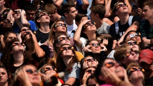 Students from Davison High School look at the solar eclipse Monday, Aug. 21, 2017 from Cardinal Stadium in Davison, Mich. (Roberto Acosta/The Flint Journal-MLive.com via AP)