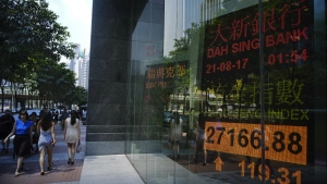 People walk past an electronic board showing Hong Kong share index outside a local bank in Hong Kong on Monday, Aug. 21, 2017. (AP / Vincent Yu)