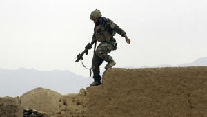 A U.S. special operations forces service member climbs down from a compound wall after investigating suspicious activity, during a joint patrol with Afghan National Army soldiers in Shewan, a former Taliban Stronghold, in Afghanistan's Farah province on Nov. 1, 2009. (AP / Maya Alleruzzo)